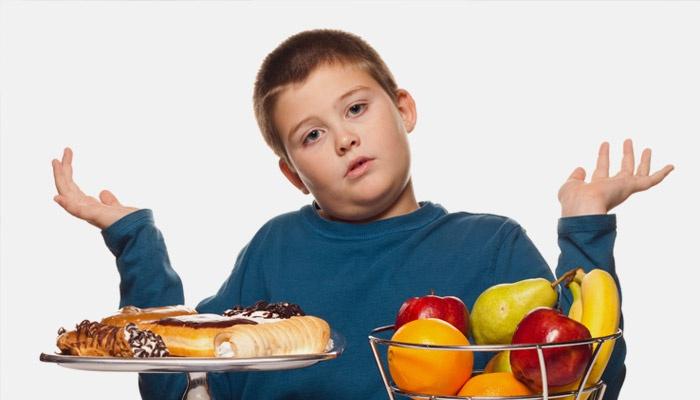 Мальчик выбирает между сладостями и фруктами