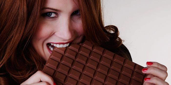 Девушка ест большую шоколадку